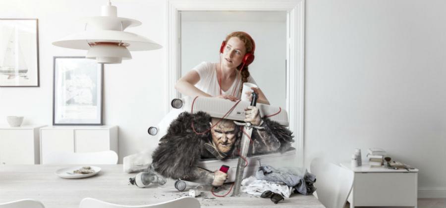 Kvinde med høretelefoner presser en viking ned i en kuffert