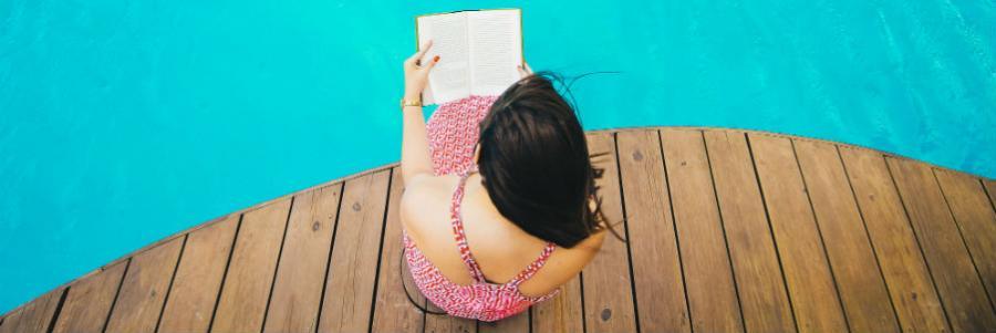 Kvinde læser ved pool