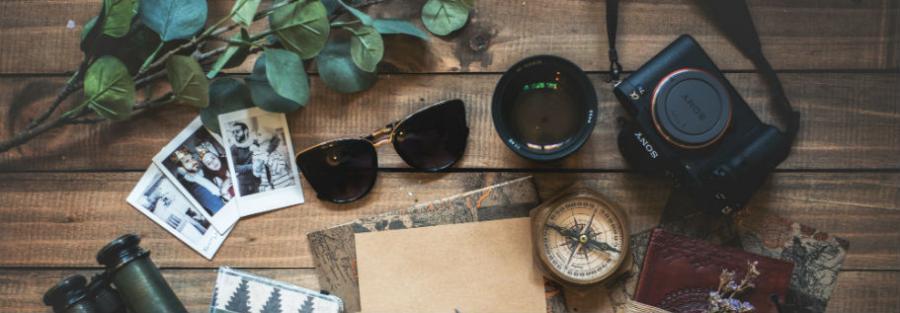 kompas, kort, solbriller og rejsedokumenter på et bord
